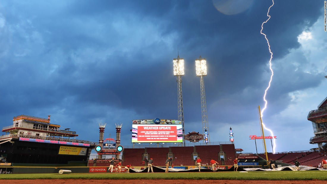 Lightning strikes in the distance as a grounds crew pulls a tarp over the field at Cincinnati's Great American Ball Park on Saturday, September 5.