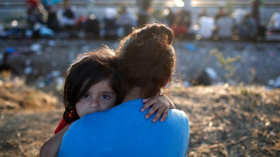 IDOMENI, GREECE - SEPTEMBER 02:  A Syrian girl is held by her mother as they wait to be processed through a border crossing into Macedonia for migrants September 2, 2015 in Idomeni, Greece.  Since the beginning of 2015 the number of migrants using the so-called