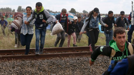 Migrants run away from a temporary holding center for asylum seekers in Roszke, southern Hungary, Tuesday, Sept. 8, 2015. Hungarian police stood by as thousands of migrants hopped cross-border trains Sunday into Austria, taking advantage of Hungary's surprise decision to stop screening international train travelers for travel visas, a get-tough measure that the country had launched only days before to block their path to asylum in Western Europe. (AP Photo/Darko Vojinovic)