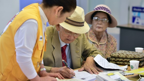 An elderly South Korean man (C) who left behind relatives in North Korea fills out applications for an expected inter-Korean family reunion programme at the Red Cross office in Seoul on September 7, 2015. North and South Korean Red Cross officials kicked off talks on September 7 on organising a rare and emotional reunion for families separated by the Korean War.  AFP PHOTO / JUNG YEON-JE        (Photo credit should read JUNG YEON-JE/AFP/Getty Images)