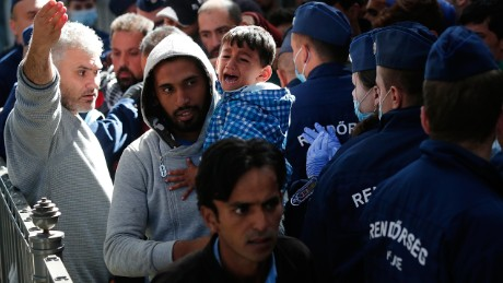 BUDAPEST, HUNGARY - SEPTEMBER 09:  A young Syrian boy cries as his father carries him past Hungarian police after being caught in a surge of migrants attempting to board a train bound for Munich, Germany at the Keleti railway station on September 9, 2015 in Budapest, Hungary. Migrants in Budapest are concerned that governments will soon close or severely limit continued travel access to Austria and Germany. Since the beginning of 2015 the number of migrants using the so-called 'Balkans route' has exploded with migrants arriving in Greece from Turkey and then travelling on through Macedonia and Serbia before entering the EU via Hungary. The number of people leaving their homes in war torn countries such as Syria, marks the largest migration of people since World War II.  (Photo by Win McNamee/Getty Images)