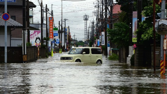 A car makes its way through a flooded street in Oyama on September 10.