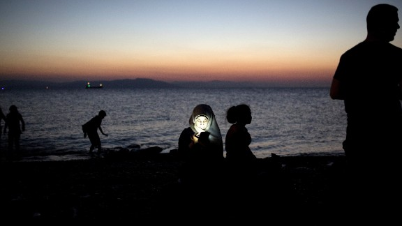 """A migrant woman checks her mobile phone after getting out of an inflatable boat on a beach on the Greek island of Kos, after crossing a part of the Aegean Sea between Turkey and Greece, on August 12, 2015. The number of migrants and refugees arriving on Greece's shores has exploded this year, but the Mediterranean country provides virtually no reception facilities and leaves them wallowing in """"totally shameful"""" conditions, a UN official said on August 7.  The UN refugee agency's division for Europe said 124,000 refugees and migrants have landed in Greece since the beginning of the year.  AFP PHOTO / ANGELOS TZORTZINIS        (Photo credit should read ANGELOS TZORTZINIS/AFP/Getty Images)"""