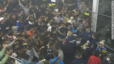 Police throw food to desperate refugees