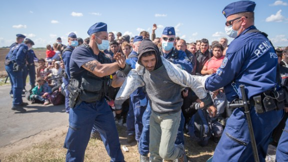 ROSZKE, HUNGARY - SEPTEMBER 07:  Migrants who have just crossed into Hungary are kept under control by the police as they wait for buses to take them to a reception camp on September 7, 2015 in Roszke, Hungary. As the migrant crisis in Europe continues and estimated 18000 people arrived in Germany over the weekend thousands more following in their wake along the Balkan route.  (Photo by Matt Cardy/Getty Images)