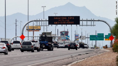 An Arizona Department of Transportation sign gives a hotline number for information on the recent freeway shootings as motorists pass under at the 202/I-10 intersection, Wednesday, Sept. 9, 2015 in Chandler, Ariz. Authorities are investigating nine shootings of vehicles over the past two weeks along I-10 in Phoenix. A truck's passenger window shattered on a Phoenix freeway Wednesday as Arizona authorities investigated a string of highway shootings that have rattled nerves and heightened fears of a possible serial shooter. (AP Photo/Matt York)
