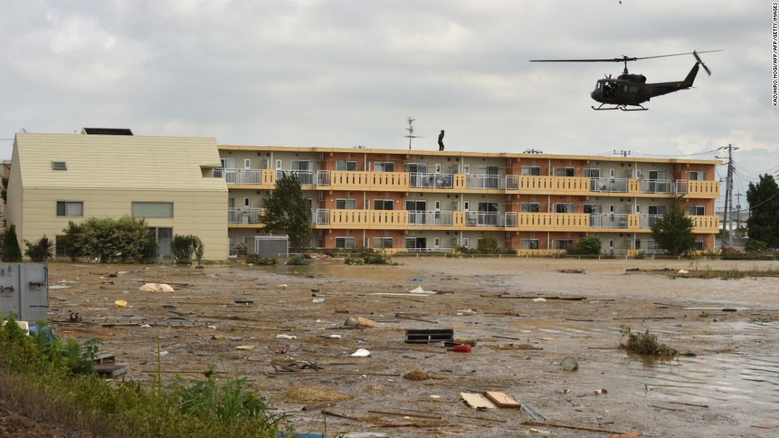 A military helicopter prepares to land on the roof of an apartment building during a rescue mission in the city of Joso in Ibaraki prefecture on Saturday, September 12.