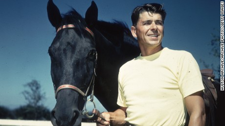 A 1935 portrait of American actor Ronald Reagan in a yellow t-shirt standing next to a black horse holding its reins.