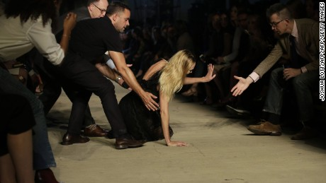 Model Candice Swanepoel receives help after falling during New York Fashion Week on September 11.