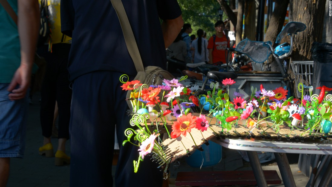Tourists pass by a tray of hair clips in a variety of forms in Nanluoguxiang, Beijing.