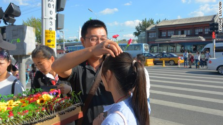 Excited tourists try on hair clips in Nanluoguxiang, a popular tourist spot in Beijing.