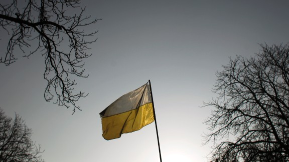 An Ukrainian flag flies in central Kiev, Monday, Feb. 24, 2014. Ukraine's acting government issued a warrant Monday for the arrest of President Viktor Yanukovych, last reportedly seen in the pro-Russian Black Sea peninsula of Crimea, accusing him of mass crimes against protesters who stood up for months against his rule. (AP Photo/Marko Drobnjakovic)