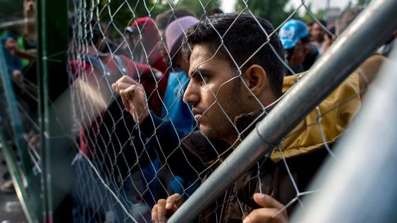A migrant looks through a fence at the closed Roszke-Horgos border crossing at the border between Hungary and Serbia near Horgos, Serbia, Tuesday, Sept.15, 2015. (Tamas Soki/MTI via AP)