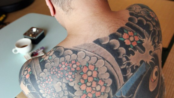 A retired yakuza boss, who does not wish to be identified, is pictured at his residence in Tokyo in 2009. His tattoo on his back features a carp swimming upstream against a waterfall.