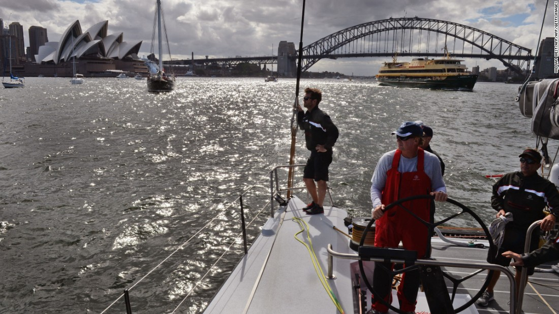 Ken Read, one of sailings most decorated yachtsman, stands at the helm of the French-designed, American-owned yacht Comanche as it sails past the Sydney Opera House and Harbor Bridge in December 2014. The boat is like nothing that has been built before and was made to push the limits of sailing.