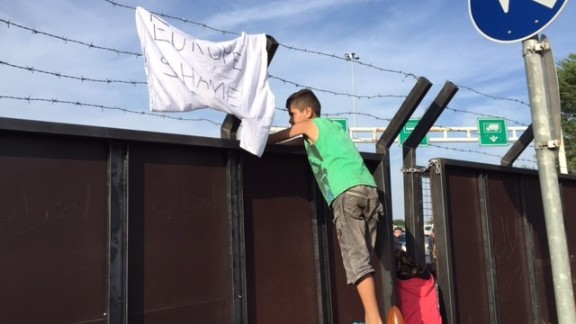Migrant children in Serbia peer across the border to Hungary.