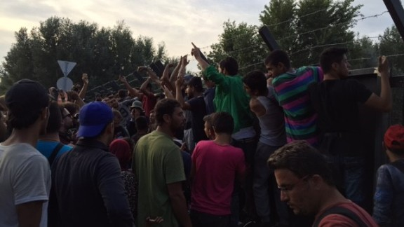 """Migrants gathered at the Serbian-Hungarian border chant, """"Open, open."""""""