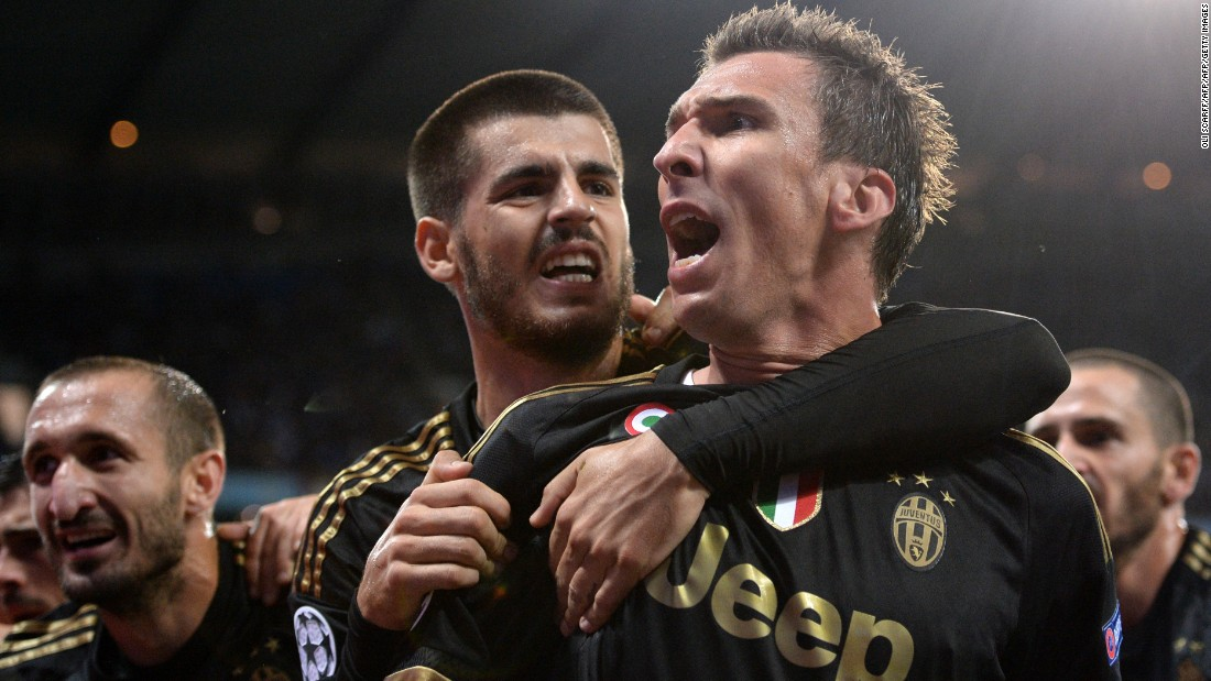 Juventus forward Mario Mandzukic (C) celebrates with Alvaro Morata (L) after scoring during a UEFA Champions League group stage football match between Manchester City and Juventus at the Etihad stadium in Manchester. Juventus won the match 2-1.