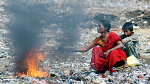 Hyderabad, INDIA: An Indian mother and her son burn waste in order to retrieve the copper wire at the garbage dump in the Borabanda slum in Hyderabad, 05 June 2007, on the occasion of World Environment Day. World Environment Day, commemorated each year 05 June, is one of the principal vehicles through which the United Nations stimulates worldwide awareness of the environment and enhances political attention and action.   AFP PHOTO / NOAH SEELAM (Photo credit should read NOAH SEELAM/AFP/Getty Images)