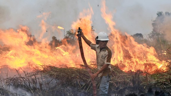 A fireman works to contain the flames on a field in Ogan Ilir, South Sumatra, Indonesia on September 12, 2015.