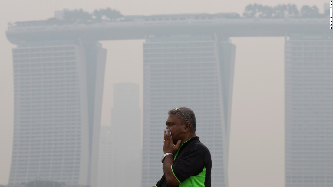 A man covers his nose near Singapore's iconic Marina Bay Sands hotel on September 10, 2015.