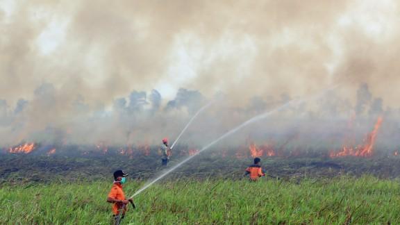 Firemen spray water to contain smoke-belching fires in Ogan Ilir, South Sumatra, Indonesia on September 5, 2015.
