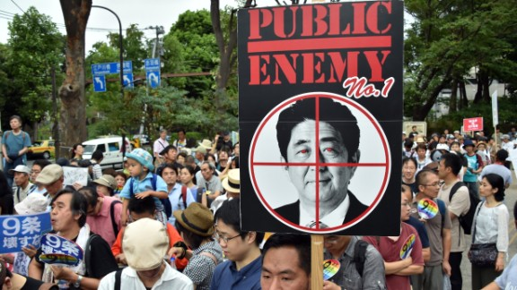 Civic group members hold placards during an anti-government rally in Tokyo on August 23, 2015.
