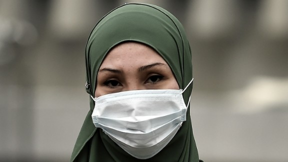"""A woman shields herself from the soupy haze with a face mask in Kuala Lumpur, Malaysia on September 15. Malaysian authorities ordered 2,045 schools in the capital and neighboring states to close on Monday after the Air Pollutant Index (API) soared to """"very unhealthy"""" levels."""