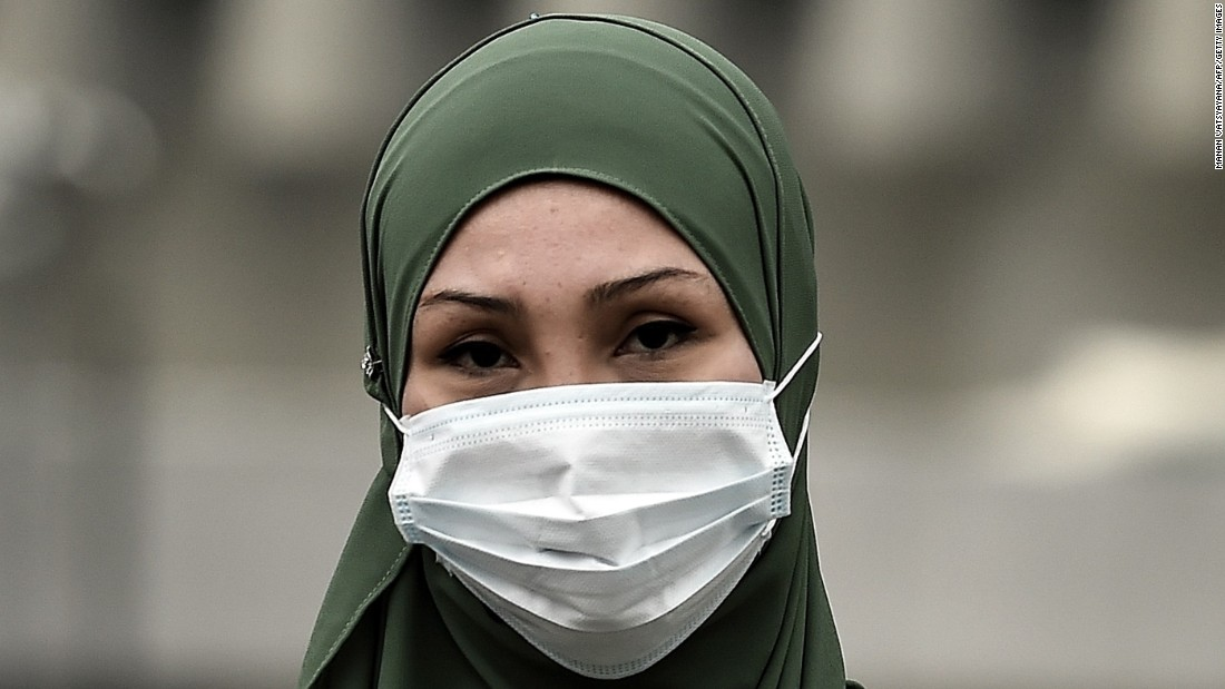 "A woman shields herself from the soupy haze with a face mask in Kuala Lumpur, Malaysia on September 15. Malaysian authorities ordered 2,045 schools in the capital and neighboring states to close on Monday after the Air Pollutant Index (API) soared to ""very unhealthy"" levels."