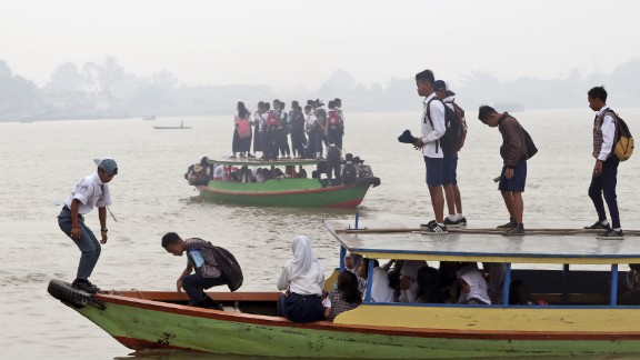 Students commute to school on boats while haze from agricultural and forest fires blankets the Ogan River in Palembang, South Sumatra, Indonesia on September 15, 2015. The thick haze caused by fires from illegal land clearing on Indonesia