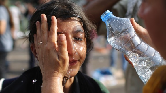 A migrant girl has stinging chemicals washed from her eyes Wednesday in Horgos, Serbia.