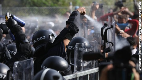 Hungarian riot police fire pepper spray and water cannons as they repel an attempt by migrants to break the border post gate and pull down the razor wire fence on September 16, 2015 in Horgos, Serbia. Hungary has introduced tough new laws to administer the influx of migrants and has declared a state of emergency in two of it's counties close to the border. The new laws have created a dead end for migrants arriving at the Horgos frontier post, resulting in clashes with migrants and Hungarian police.