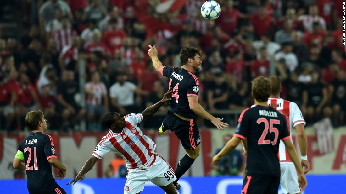 Bayern Munich's Xabi Alonso battles for a high ball with Olympiakos forward Ideye Brown in the Group F game in Greece. Bundesliga champions Bayern were made to work hard before breaking through.