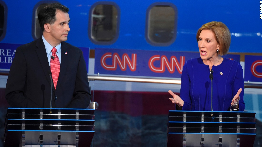 Walker watches Fiorina answer a question.