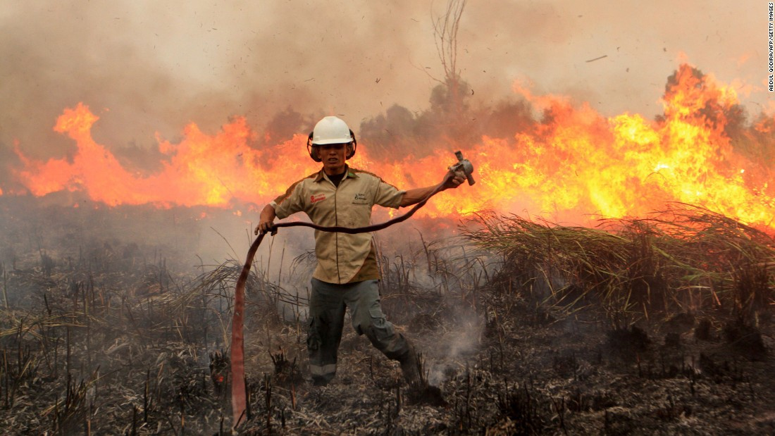 A firefighter combats a blaze in Ogan Komering Ilir, Indonesia, on Saturday, September 12.