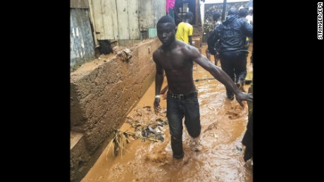 A man walks Thursday along a flooded street in Freetown, Sierra Leone, which has been drenched by days of heavy rain.