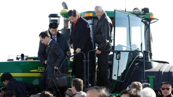 Then-Vice President Xi (2nd R) climbs out of the cab of a tractor with Rick Kimberley (R) while touring his family farm on February 16, 2012 in Maxwell, Iowa.