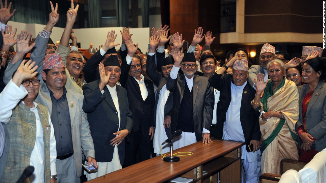 Nepalese Prime Minister Sushil Koirala, Unified Marxist Leninist chairman K P Oli, Nepalese Unified Communist Party of Nepal (Maoist) chairman Pushpa Kamal Dahal, known better as Prachanda and other lawmakers wave while Nepal's parliament passes a new national constitution in Kathmandu on September 16, 2015.