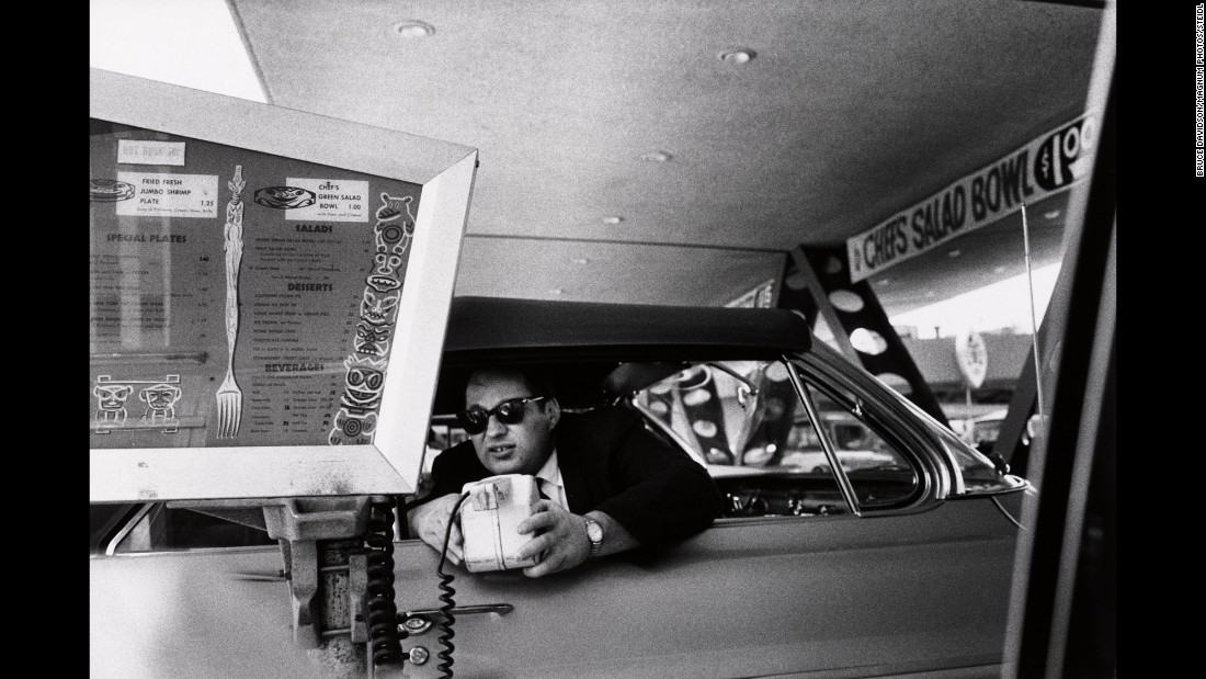 "A man uses a microphone to order food from a drive-in diner. This photo was also used as the cover of the Beastie Boys album ""Ill Communication."""