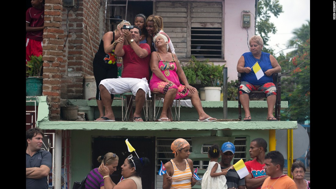 Residents wait for Pope Francis to drive past in Holguin, Cuba, on September 21.