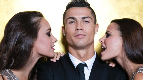 """Cristiano Ronaldo poses with models as he unveils his debut fragrence """"Cristiano Ronaldo Legacy"""" at a launch party on September 9, 2015 in Madrid, Spain. Ronaldo's global popularity has grown thanks to the work of his agent Jorge Mendes."""