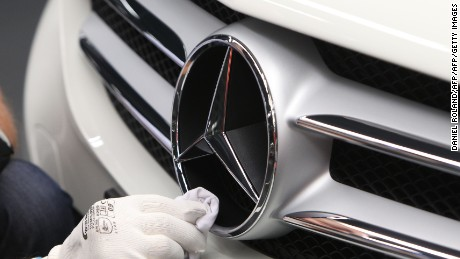 An employee polishes the logo of a car at the Mercedes-Benz factory in Germany.