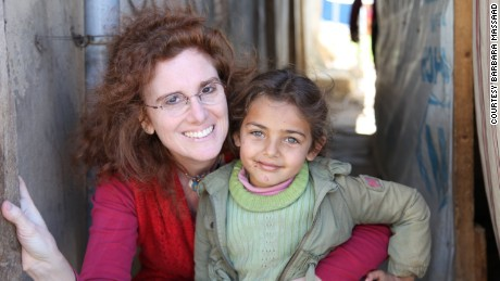 "Barbara Massaad poses with a refugee child at the Hamra Street refugee camp in Beirut. Her experience at this camp inspired her to create the humanitarian cookbook ""Soup for Syria""."