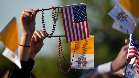 People wave U.S. and Vatican flags as they wait for the Pope's arrival at the White House on September 23.