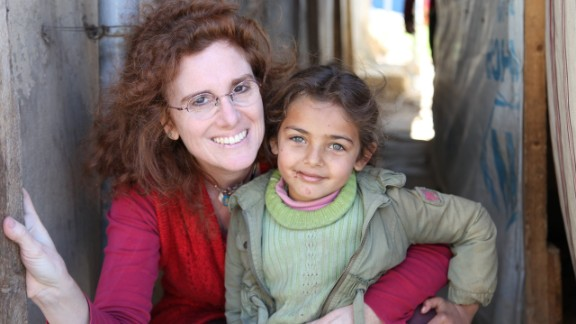 """Barbara Massaad poses with a refugee child at the Zahle Lebanon. Her experience at the camp inspired her to create the humanitarian cookbook """"Soup for Syria."""""""