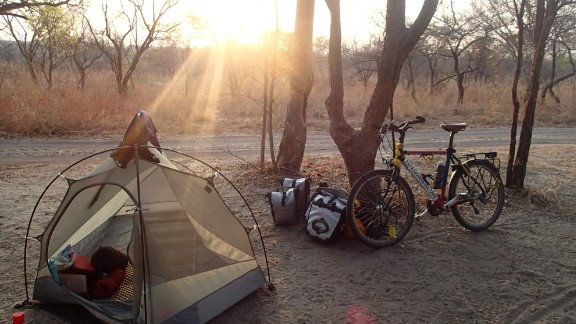 Rutland's bicycle and second tent, camped in the Ugandan bush. He lost his first tent in a fire on his first night in the Mozambique bush, which he started by knocking over his gas stove.