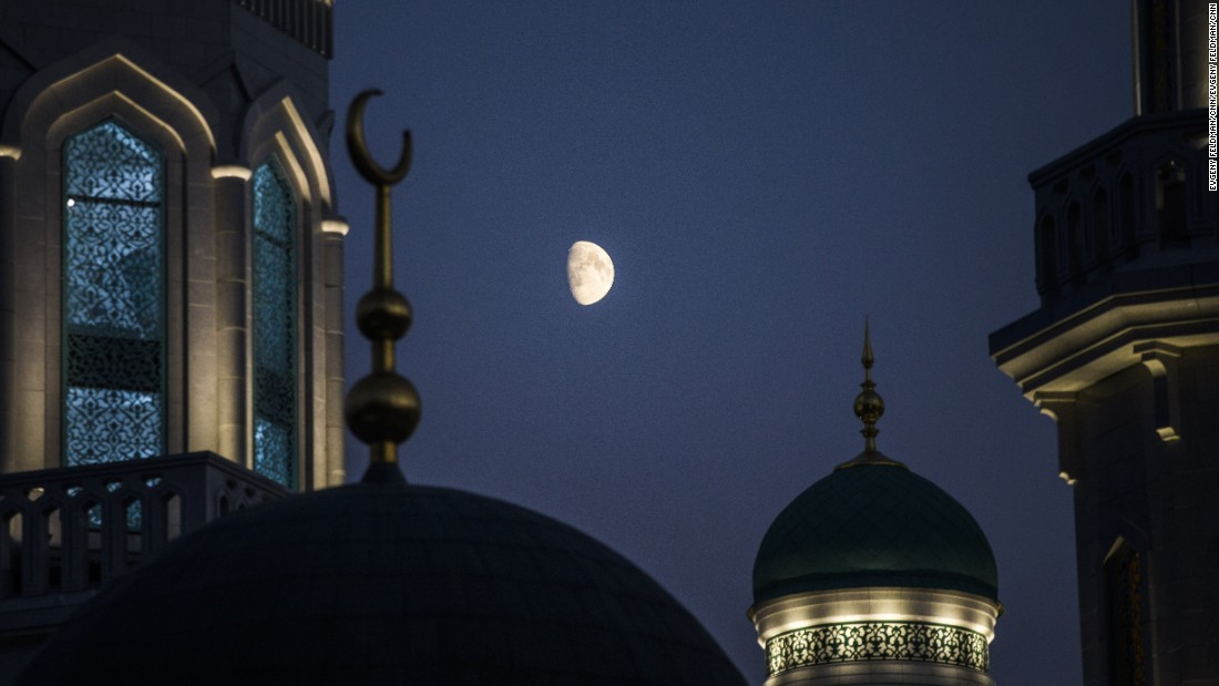 The moon rises over the mosque.