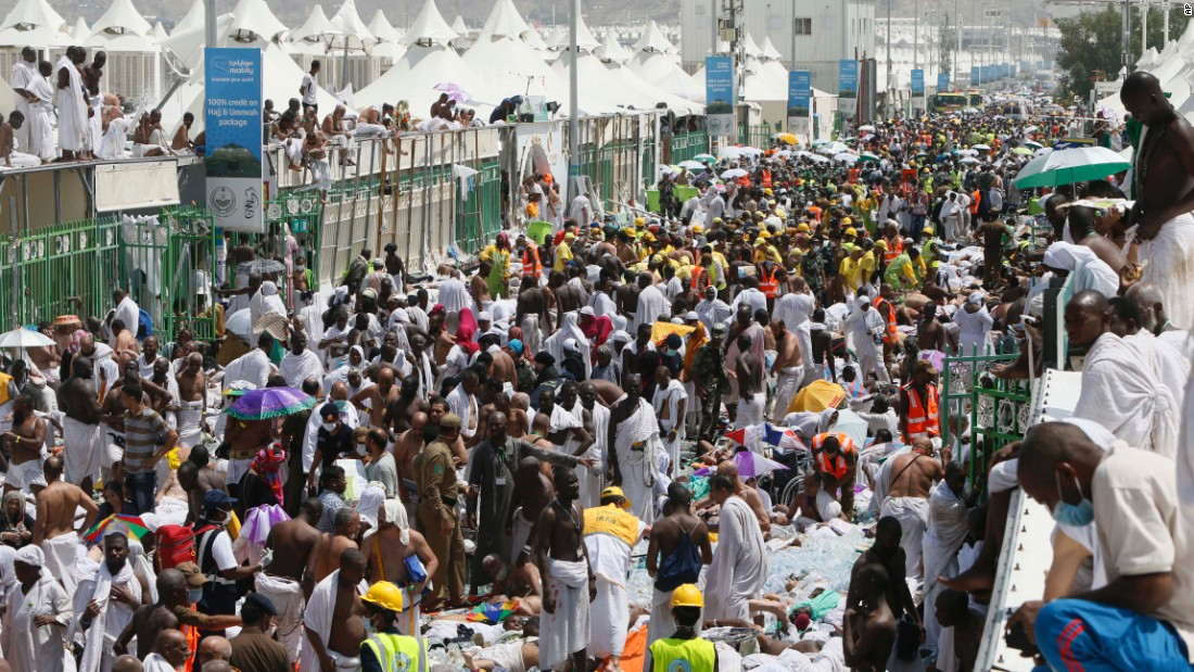 Muslim pilgrims and rescuers gather around the victims.