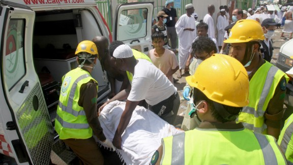 Saudi emergency personnel load a wounded pilgrim into an ambulance.