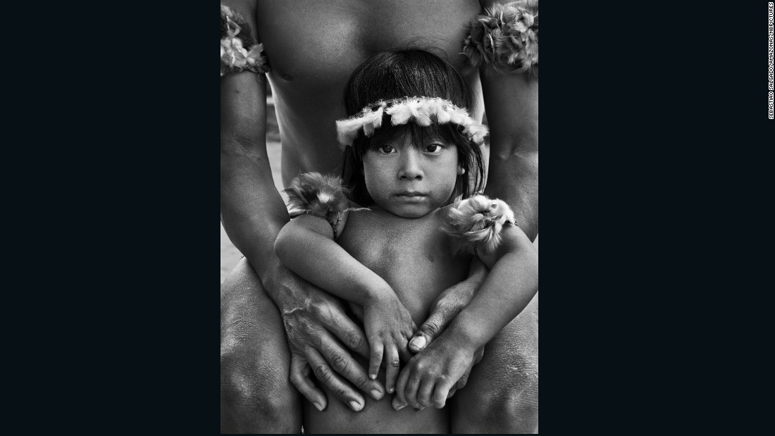 "Revered Brazilian photographer Sebastiao Salgado has traveled to over 100 countries to document social issues. He is a UNICEF Goodwill Ambassador and has won numerous photography prizes.<br /><br />This photo of a son in his fathers arms is part of Salgado's series on the Awa tribe.<br />Salgado: ""My images of the Awa, a nomadic hunter-gatherer tribe of the north-eastern Brazilian Amazon, reveal the devastating consequences of deforestation. They shed light on the lives of the Awa, who have become knows as Earth's most threatened tribe."""